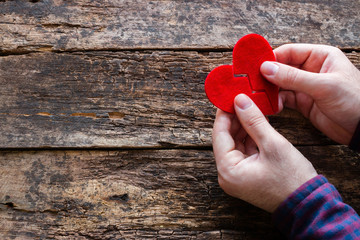 man holding two halves of a broken heart on the wooden background