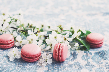 Pink macaroons and blooming cherry flowers at vintage tablecloth