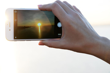 Female hand holding smart phone and taking photo of sunset