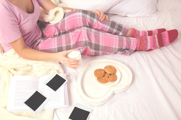 Woman in pajamas looking at photos on her bed