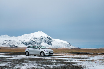 Road in the mountains with the white travel car. Wonderful nature in winter Iceland