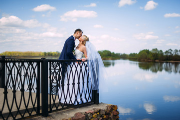 happy and beautiful groom and bride tender kiss at spring outdoo