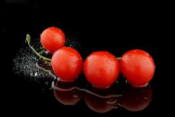 ein strauch tomaten auf wasser mit schwarzen hintergrund