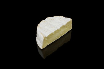 ein stück camembert käse auf schwarzen hintergrund