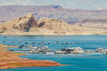Sunny day at Lake Powell with many boats and canyon in the background