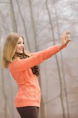 Lovely fashion woman in park taking selfie photo.