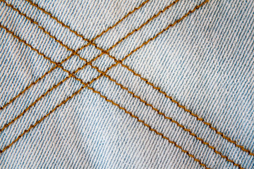 Crisscrossing tan stitching on jean fabric