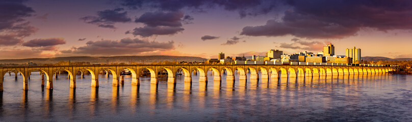 Wall Mural - Philadelphia and Reading Railroad Bridge crosses Susquehanna river at sunset. Harrisburg skyline shines under a late afternoon light.