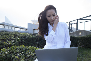 Asian woman is using a laptop sitting in the park