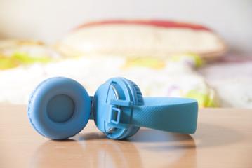 Blue headphone in bedroom background