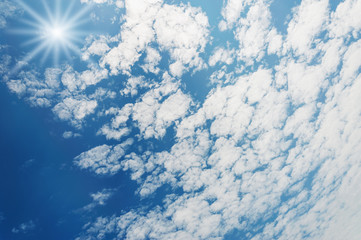 Blue sky with shape of white cloud and sunrays