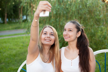 Smiling teenage girls taking self photo with cellular phone