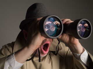 Photograph of an NSA agent in trench coat and hat looking through binoculars. The agent is shocked to see an FBI agent watching him.