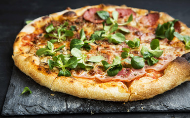 Pizza salami,cheese and ham with cornsalad leaves