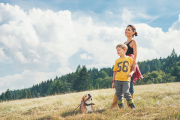 Fototapete - Mother with son and his dog walk on the golden field