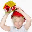Cute girl with helmet and a house