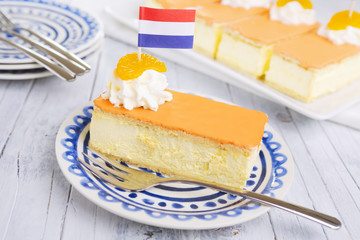 Orange tompouce, traditional Dutch pastry, on a rustic table