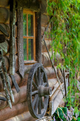wheel from an old cart near wooden rural house