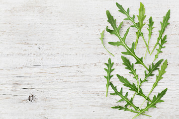 Rucola, salad rocket, rucoli, rugula, colewort, roquette or arugula on wooden rustic table, top view