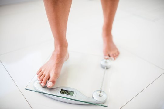 Womans feet going on weighting scale