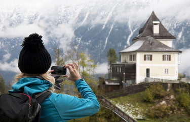 Young beautiful women taking picture of Alps landscape, Austria