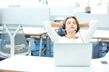 Carefree pretty woman sitting and relaxing on workplace in office