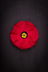 Flower poppy red crocheted from threads on a black background, a