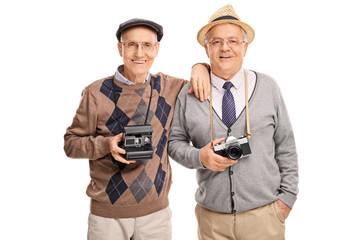 Two senior gentlemen holding cameras