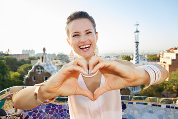 Woman tourist showing heart shaped hand in Park Guell, Barcelona