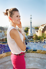 Happy woman listening audioguide in Park Guell, Barcelona, Spain