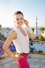 Foto op Canvas Las Vegas Smiling woman listening audioguide in Park Guell, Barcelona
