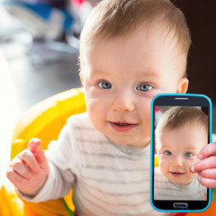 Baby boy taking selfie with a cell phone camera