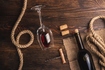 Glass with wine, bottle, corkscrew and burlap, wooden background