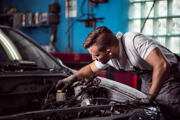 Car mechanic repairing vehicle