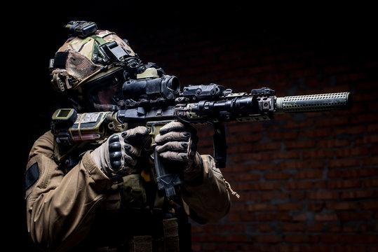 Spec ops soldier in uniform with assault rifle/man in military uniform with assault rifle aiming at target on background of dark wall