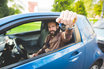 Young handsome caucasian bearded man sitting in his car, holding