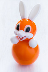 Roly-poly toy rabbit in orange on a white background