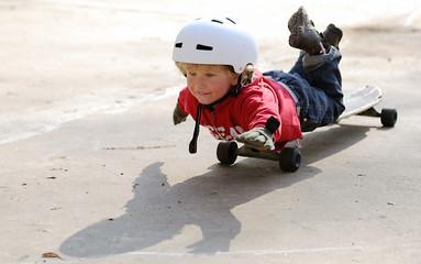 Kleiner junge liegt auf Skateboard