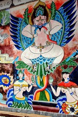 Guan Yin Xia, China - April 22, 2006:   Painted frescoes in a pseudo-Hindu style on a Naxi home depict a winged deity flanked by two women