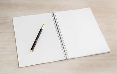 Open notebook with pen white lined pages on wooden office desk .