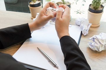 Hands of woman crumple sheets of Resume at the desk, mistake