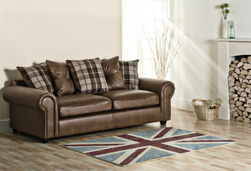 Brown Leather sofa in modern living room with fireplace, basket and logs