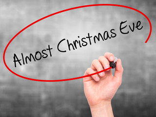 Man Hand writing Almost Christmas Eve with black marker on visua