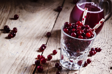 Cheerful funny juice from cranberries, berries with straws in a