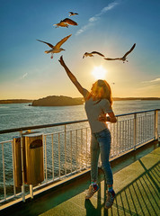 Young girl feeding seagulls in the flare of setting sun onboard a ferry in Scandinavia
