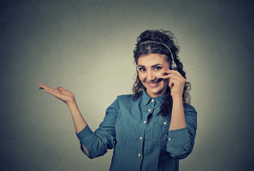 Smiling female customer representative with phone headset pointing at copy space