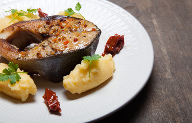 Fried tuna fish with mashed potato, dried tomato and parsley on