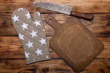 Retro cutting board, pot holder and knife on old wooden burned t