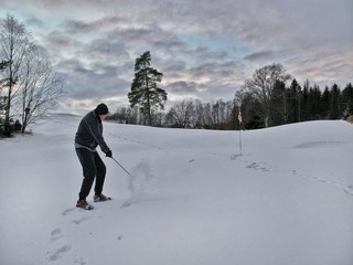 All is possible. Old golfer hits the ball with the club in deep snow