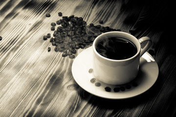Coffee beans and coffee in white cup on wooden table. Selective